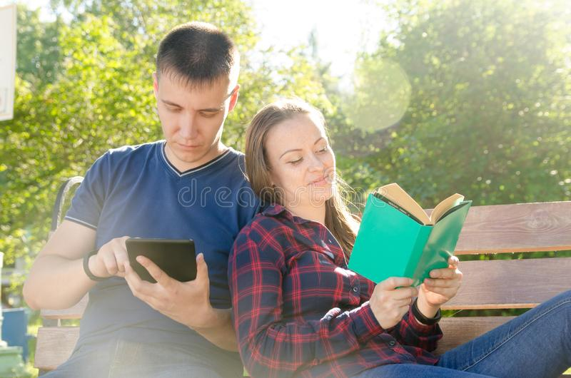 Guy reads book on the tablet next to the sitting girl reads book in summer sunny day in park stock photography