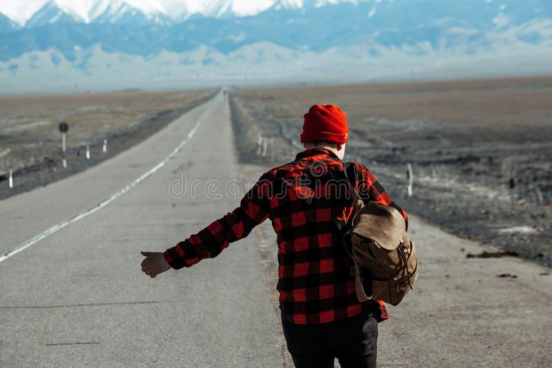 Guy in red hitchhiking down on lonesome road. Guy dressed in red with backpack hitchhiking down on long lonesome road stock image