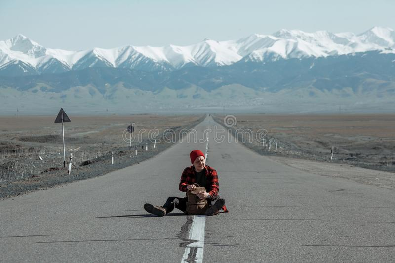 Guy sitting on ground and looking far away. Guy in red shirt and with leather travelling backpack sitting on ground and looking far away with mountains in stock images