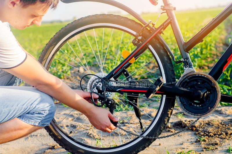 The guy repairs the bicycle. chain repair. cyclist. unratitude on the road, travel, close-up. The guy repairs the bicycle. chain repair. cyclist. unratitude on royalty free stock photography