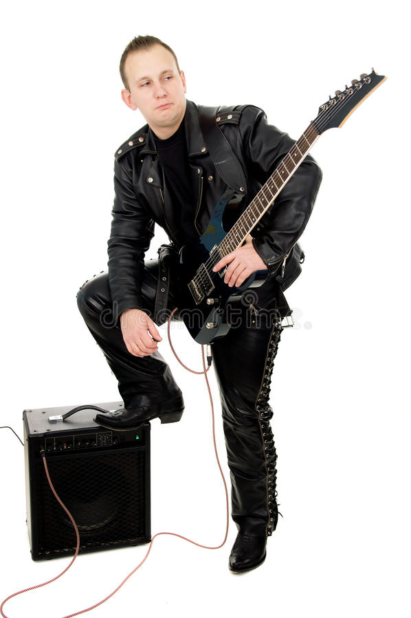 Guy rock guitarist in leather garments, plays guitar. Isolated on white background royalty free stock image