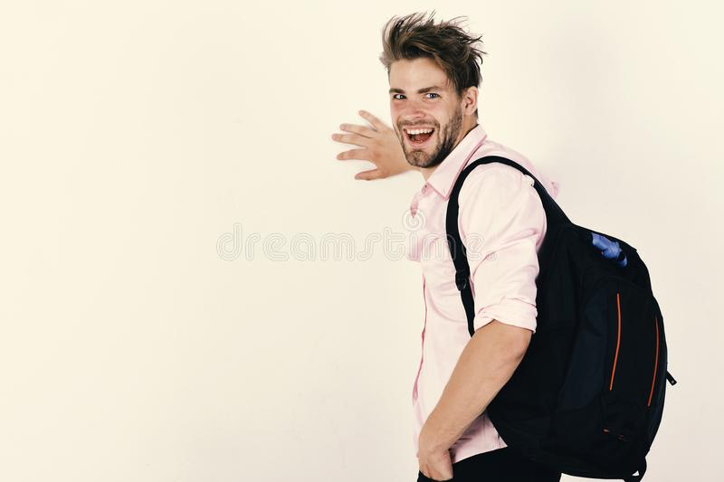 Guy with rucksack and happy face. Young man backpacker walking in studio royalty free stock images
