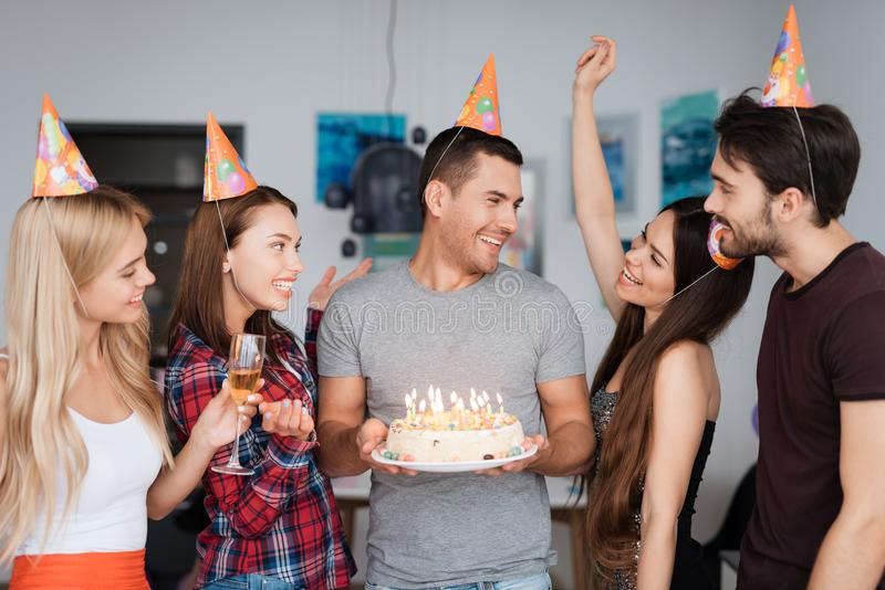 A guy`s birthday and his friends congratulate him. Guests are standing around the birthday boy. The guy is holding a royalty free stock image
