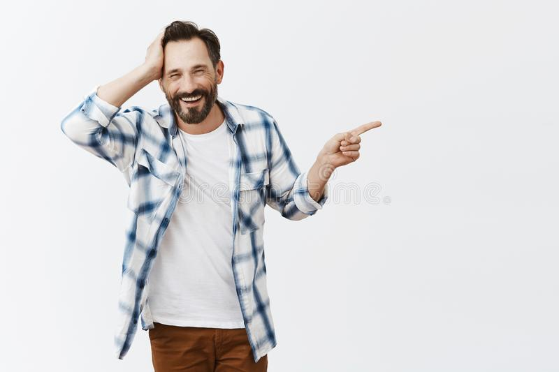 Guy saying sorry, coming in wrong place by mistake, holding palm on head and pointing right while explaining what royalty free stock image