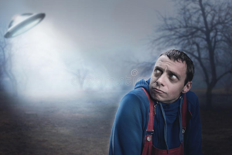 Guy scared by UFO. In the night stock images
