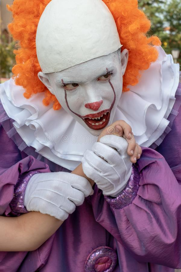 A guy in a scary clown costume with sharp teeth holds someone else`s hand and pretends to want to bite her off. Cosplay to royalty free stock photo