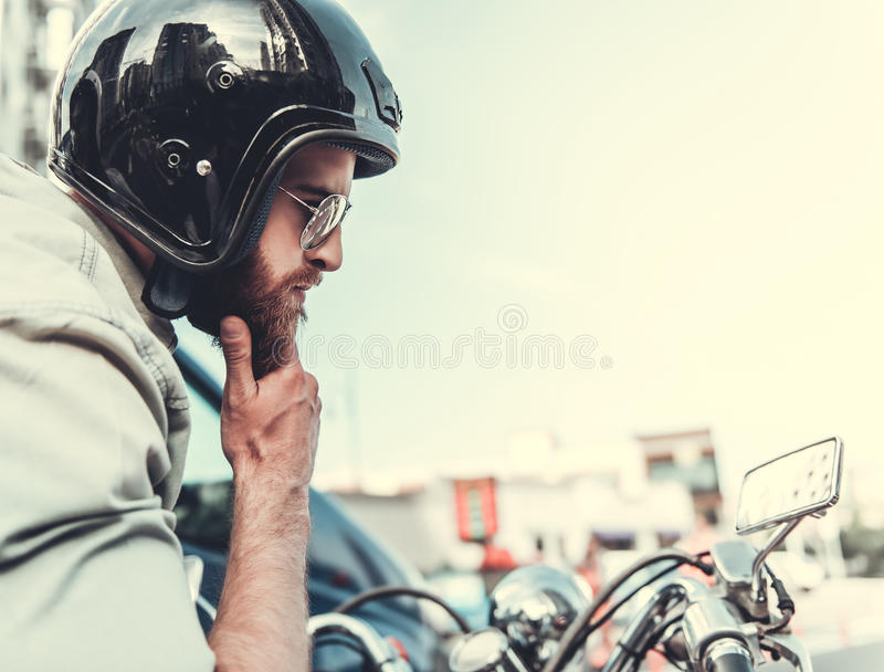 Guy on scooter. Side view of handsome bearded guy in sun glasses and helmet rubbing his chin while sitting on a scooter royalty free stock photography