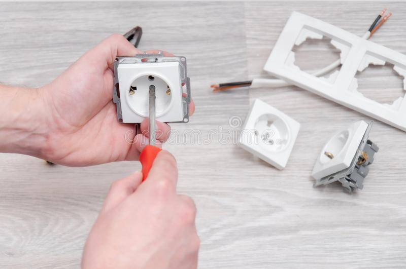 The guy sets the sockets in the room. Repair in the house. royalty free stock photo