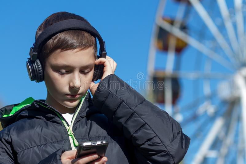 The guy sets up the phone to listen to music in the headphones next to the Ferris wheel. stock images