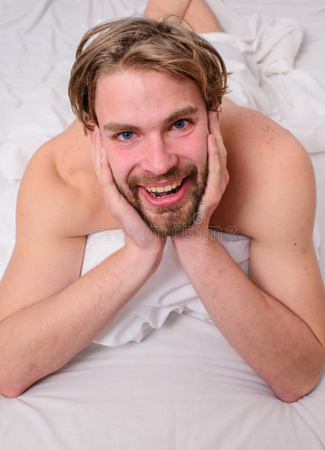 Guy macho lay white bedclothes. Playful mood concept. Man unshaven handsome happy smiling torso relaxing bed. Pleasant relax concept. Man feel full of energy stock photography