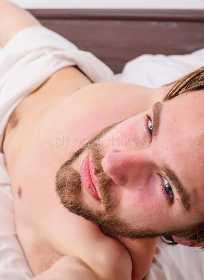 Guy macho lay white bedclothes. Playful mood concept. Man unshaven handsome torso relaxing bed. Pleasant relax. Concept. Man feel satisfied after pleasant night stock photography