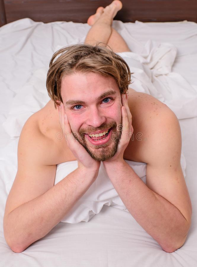 Guy macho lay white bedclothes. Pleasant relax concept. Playful mood concept. Man unshaven handsome happy smiling. Torso relaxing bed. Man feel full of energy stock image