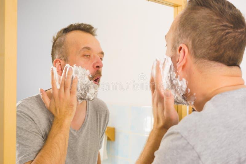 Guy shaving his beard in bathroom stock photography