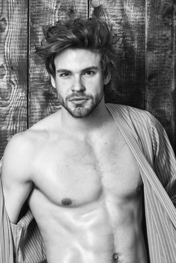 Guy shimmering skin undressing bathrobe. attractive macho tousled hair on wooden background. Man athlete with fit. Torso. Sportsman show six pack torso stock image