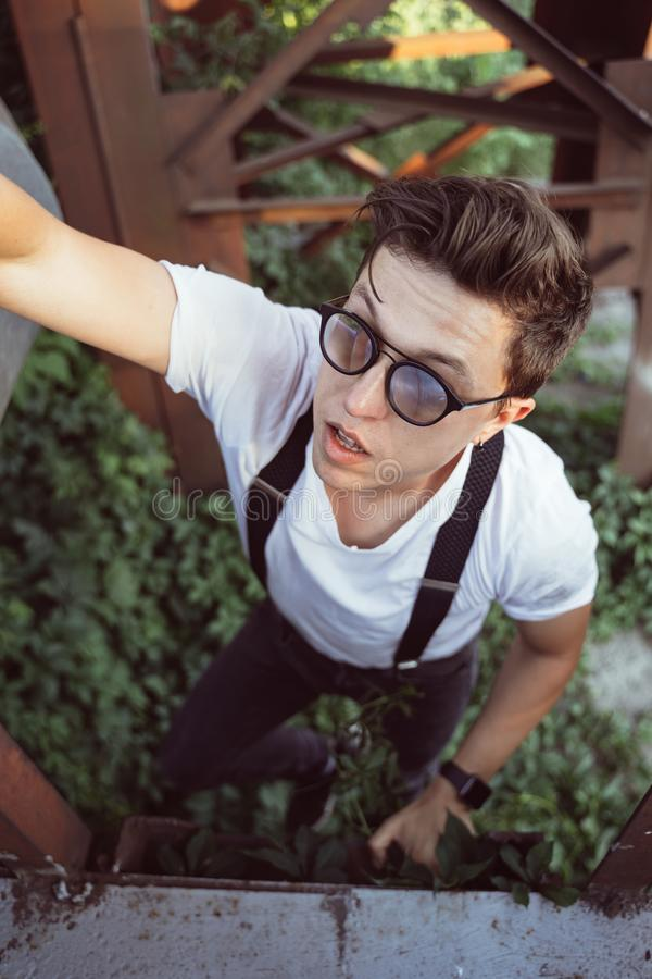Guy in a shirt with suspenders among old metal structures stock photo
