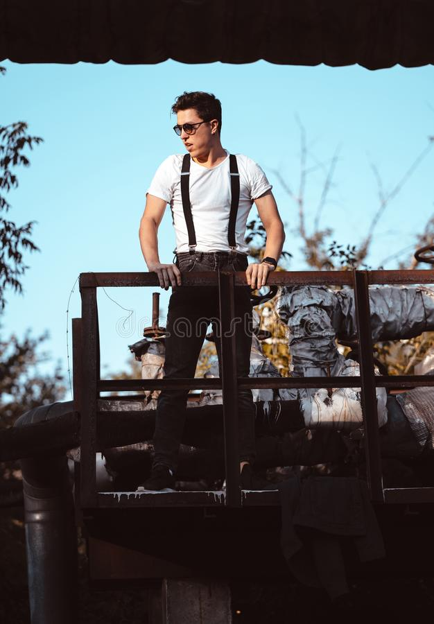 Guy in a shirt with suspenders posing at old pipes royalty free stock photography