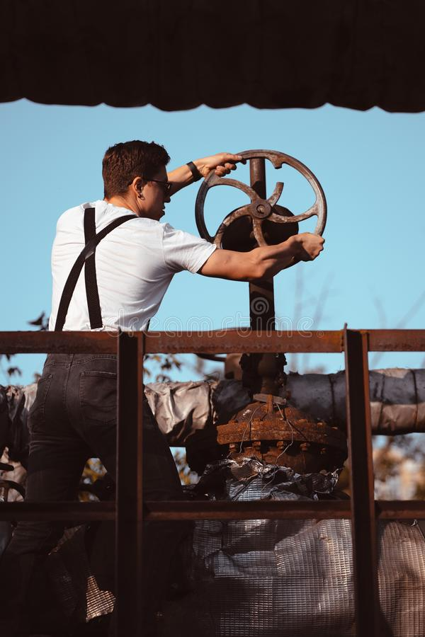 Guy in a shirt with suspenders turns the old valve stock images