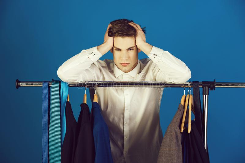 Guy in the shirt and tie in closet with clothes royalty free stock image