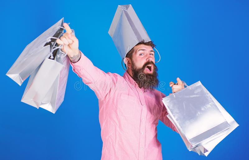 Guy shopping on sales season with discounts. Hipster on cheerful face with bag on head is addicted shopaholic. Man with. Beard and mustache carries shopping royalty free stock photo