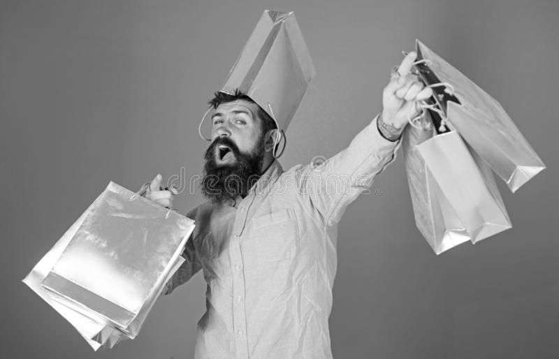 Guy shopping on sales season with discounts. Hipster on cheerful face with bag on head is addicted shopaholic. Man with. Beard and mustache carries shopping stock photos