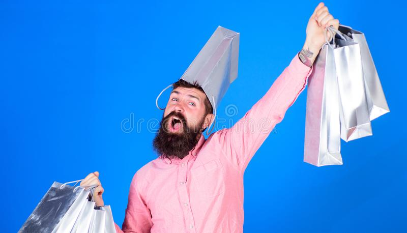 Guy shopping on sales season with discounts. Hipster on happy face with bag on head is addicted shopaholic. Shopping. Concept. Man with beard and mustache royalty free stock images