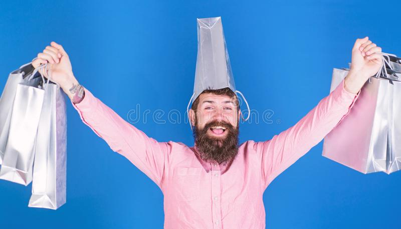 Guy shopping on sales season with discounts. Man with beard and mustache carries shopping bags, blue background. Shopping concept. Hipster on happy face with stock photo