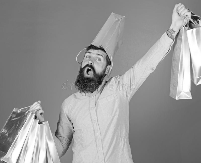 Guy shopping on sales season with discounts. Man with beard and mustache carries shopping bags, blue background. Hipster. On happy face with bag on head is stock images