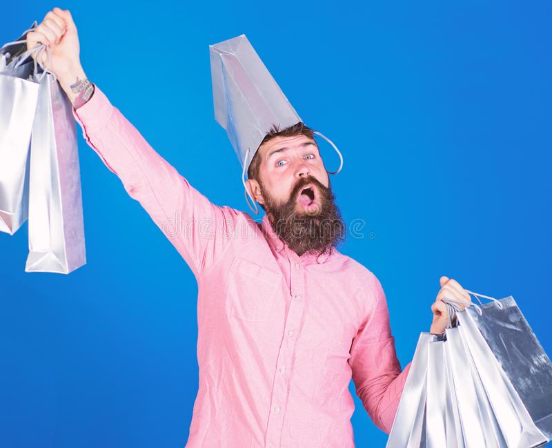 Guy shopping on sales season with discounts. Man with beard and mustache carries shopping bags, blue background. Hipster. On happy face with bag on head is stock image