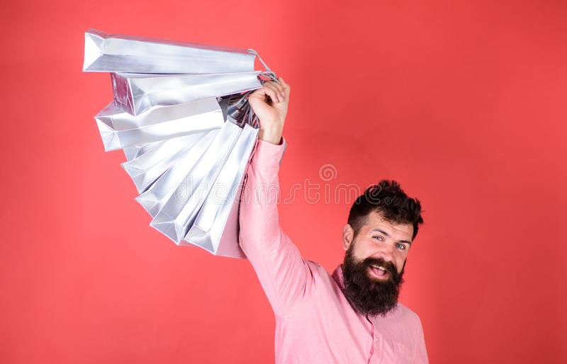 Guy shopping on sales season with discounts. Man with beard and mustache holds shopping bags, red background. Hipster on. Happy face is shopping addicted or royalty free stock photos