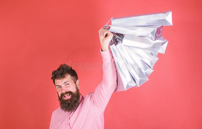 Guy shopping on sales season with discounts. Man with beard and mustache holds shopping bags, red background. Hipster on. Happy face is shopping addicted or stock photography