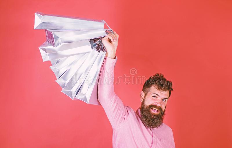 Guy shopping on sales season with discounts. Man with beard and mustache holds shopping bags, red background. Hipster on. Happy face is shopping addicted or royalty free stock image