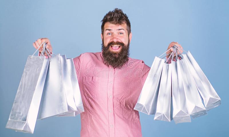Guy shopping on sales season with discounts. Sale and discount concept. Hipster on happy face is shopping addicted or. Shopaholic. Man with beard and mustache stock photo
