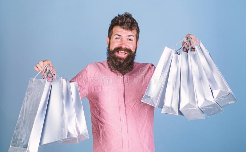 Guy shopping on sales season with discounts. Sale and discount concept. Man with beard and mustache hold shopping bags. Light blue background. Hipster on happy royalty free stock photography
