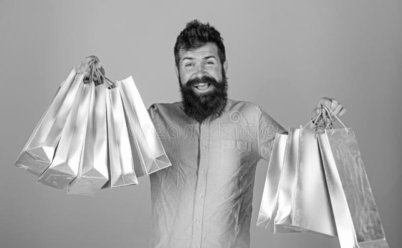 Guy shopping on sales season with discounts. Sale and discount concept. Man with beard and mustache hold shopping bags. Light blue background. Hipster on happy stock photography