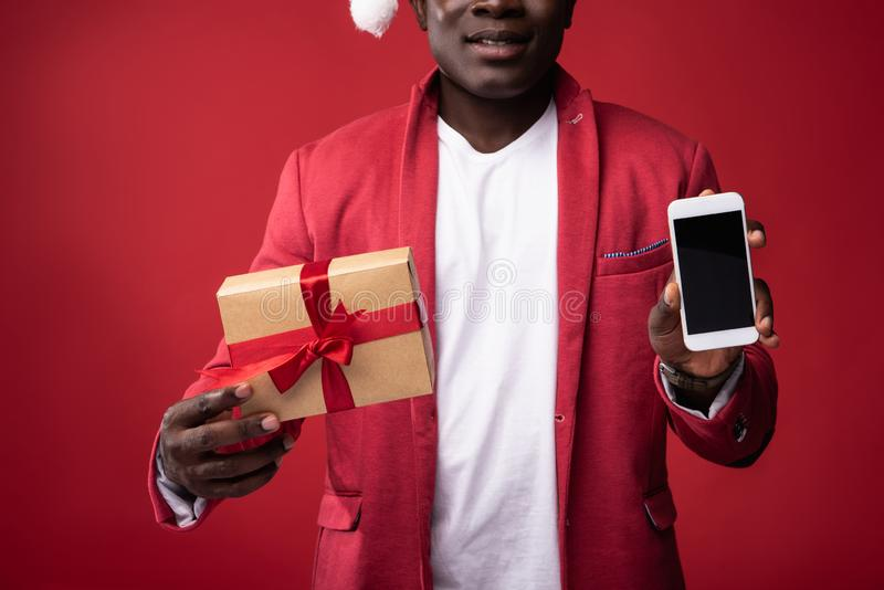 Guy is showing smartphone and new year present. Good stuff. Smiling guy in santa hat holding gift box with ribbon and mobile phone. on red background stock photography
