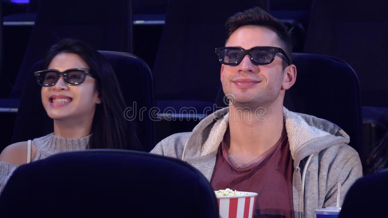 Guy sit between two girls at the movie theater stock photos
