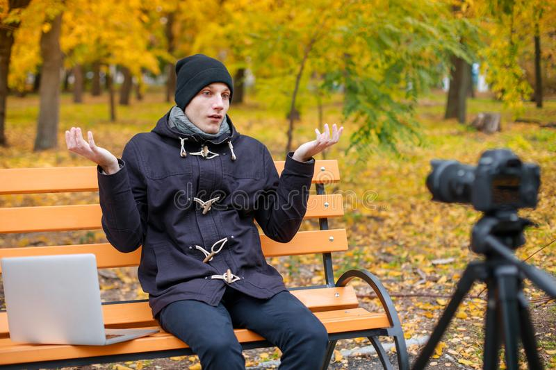 A guy sits in an park on a bench with a laptop in front of a camera on a tripod and disappointed with hands. stock images