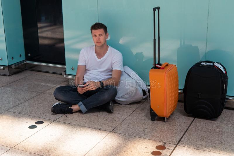 The guy is sitting on the floor at the airport. Brunette in a white T-shirt stock images