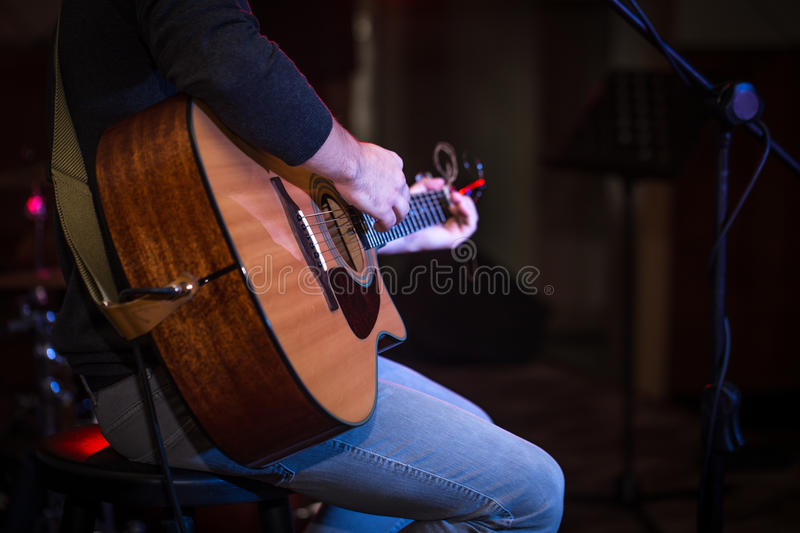 guy sitting in a high chair and playing acoustic guitar royalty free stock photos