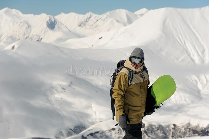 Guy in ski equipment is holding a green snowboard. Guy in ski equipment and glasses is holding a green snowboard on the background against the snowy mountains royalty free stock images