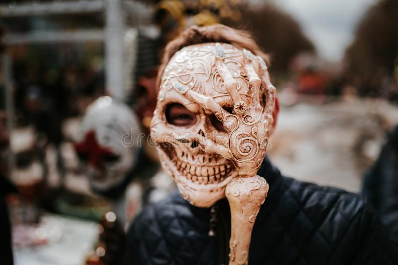 Guy in skull mask in the street in time of carnival or Helloween. Skeleton mask royalty free stock photo