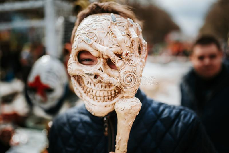 Guy in skull mask in the street in time of carnival or Helloween. Skeleton mask. Photo of guy in skull mask in the street in time of carnival or Helloween royalty free stock photos