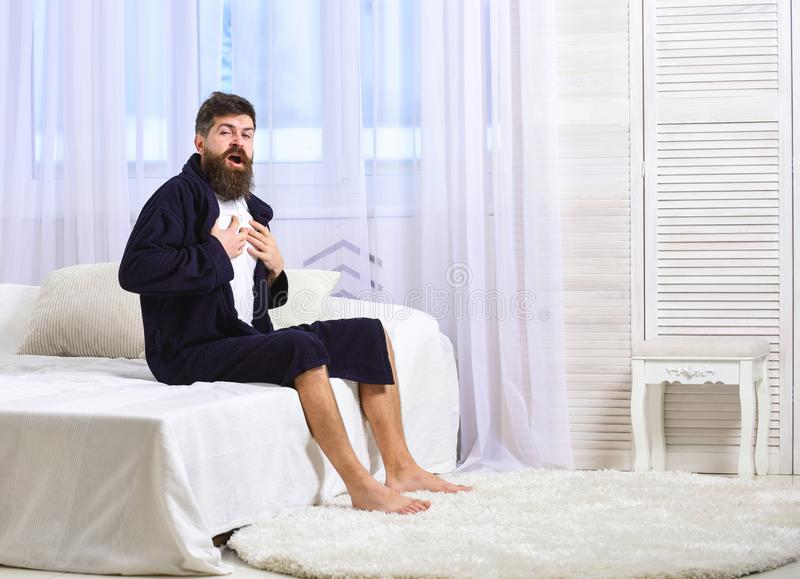 Guy on sleepy face yawning in morning. Awakening concept. Macho with beard and mustache sluggish yawning, relaxing after. Nap, rest. Man in robe sits on bed stock photo