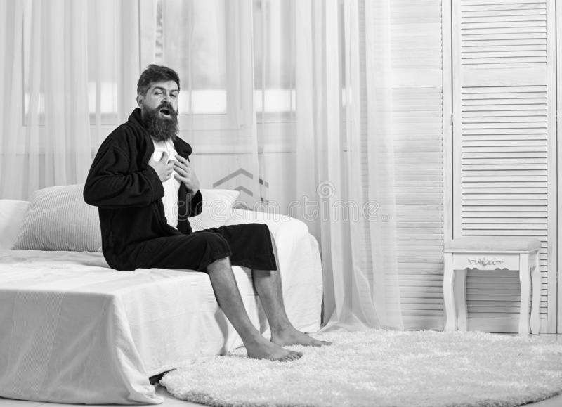 Guy on sleepy face yawning in morning. Awakening concept. Macho with beard and mustache sluggish yawning, relaxing after. Nap, rest. Man in robe sits on bed royalty free stock photo