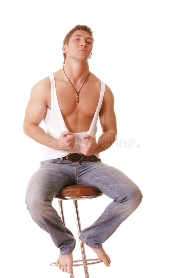 Guy In Sleeveless Shirt And Jeans Sitting On Chair Royalty Free Stock Photos