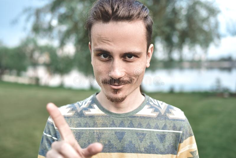 A guy with a sly expression on his face, shows a finger gesture, says do not try to deceive me. A guy with a sly expression on his face, shows a finger gesture stock image