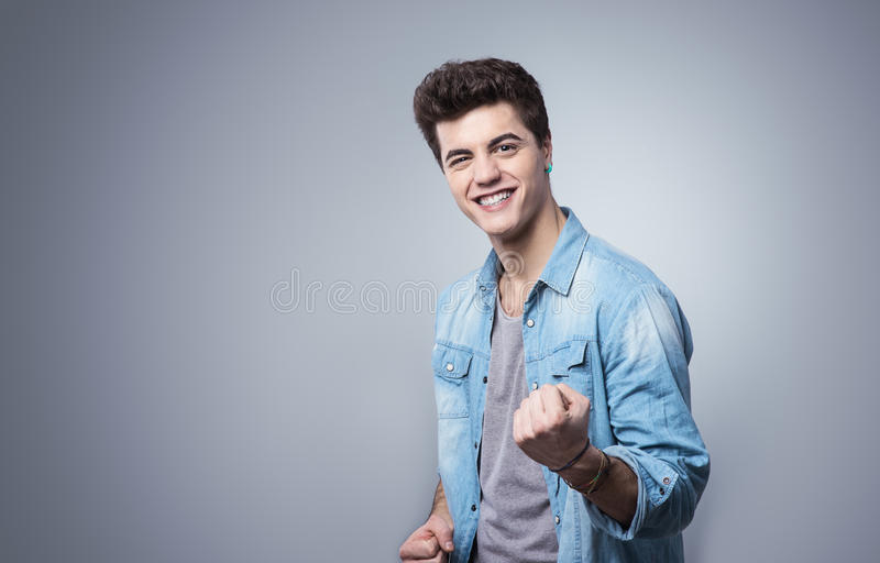 Guy smiling and showing fists. Smiling cheerful guy showing fists with playful attitude royalty free stock photos