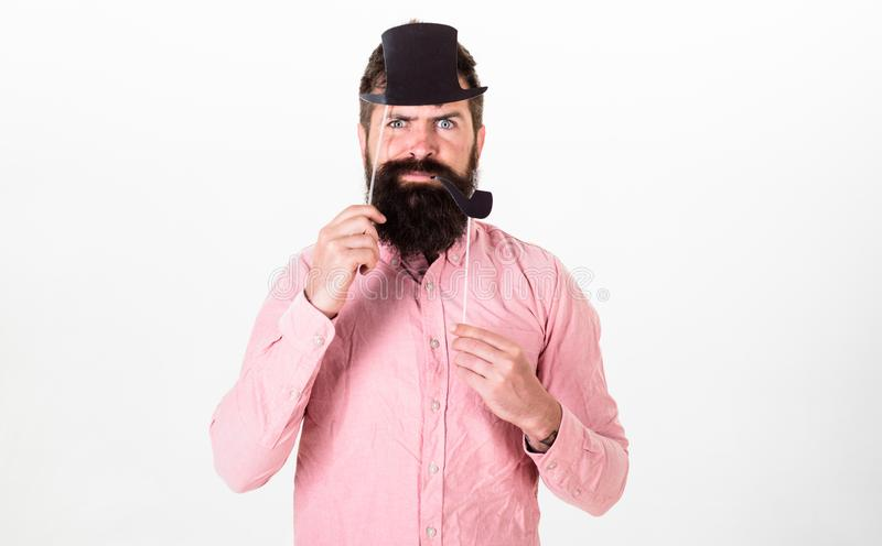 Guy smokes tobacco pipe. Hipster with beard and mustache on serious face posing with photo booth props. Aristocracy. Concept. Man holding paper party props royalty free stock image