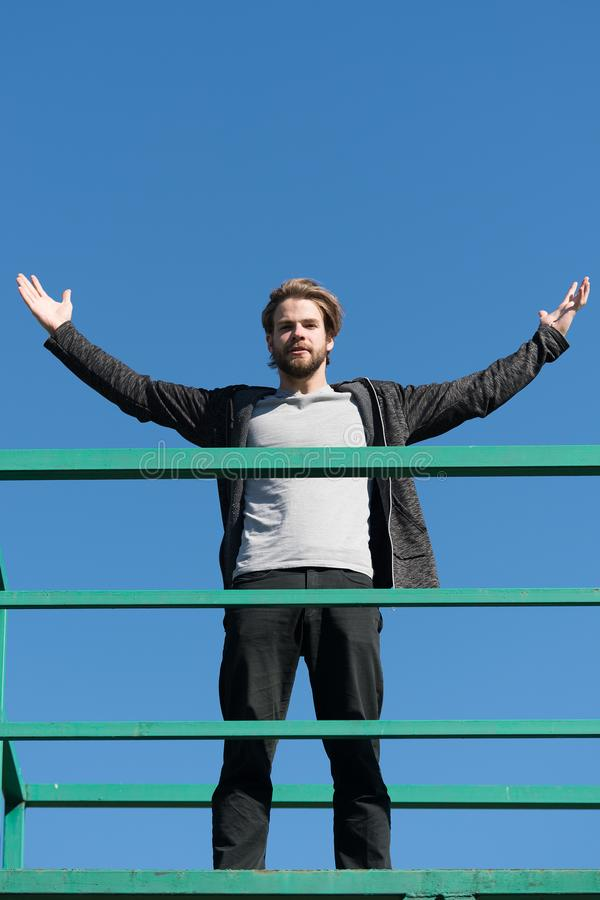 Guy stand high on rooftop terrace on blue sky. Bearded man with raised hands on sunny outdoor. Success and future concept. Man fas royalty free stock images