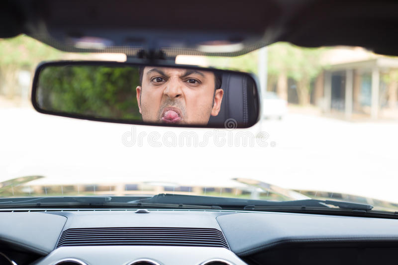 Guy sticking tongue out in rearview mirror stock photography